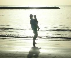 mother holding child beach sillhouette