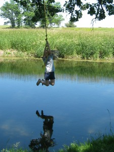 child rope swinging over creek